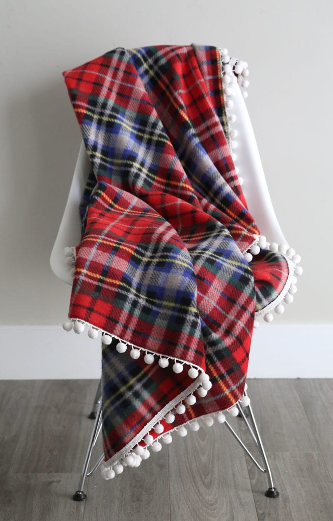20+ Christmas Sewing Projects featured by top US craft blogger, Sweet Red Poppy: It's Always Autumn Fleece Blanket With Pom Pom Trim Sewing Tutorial