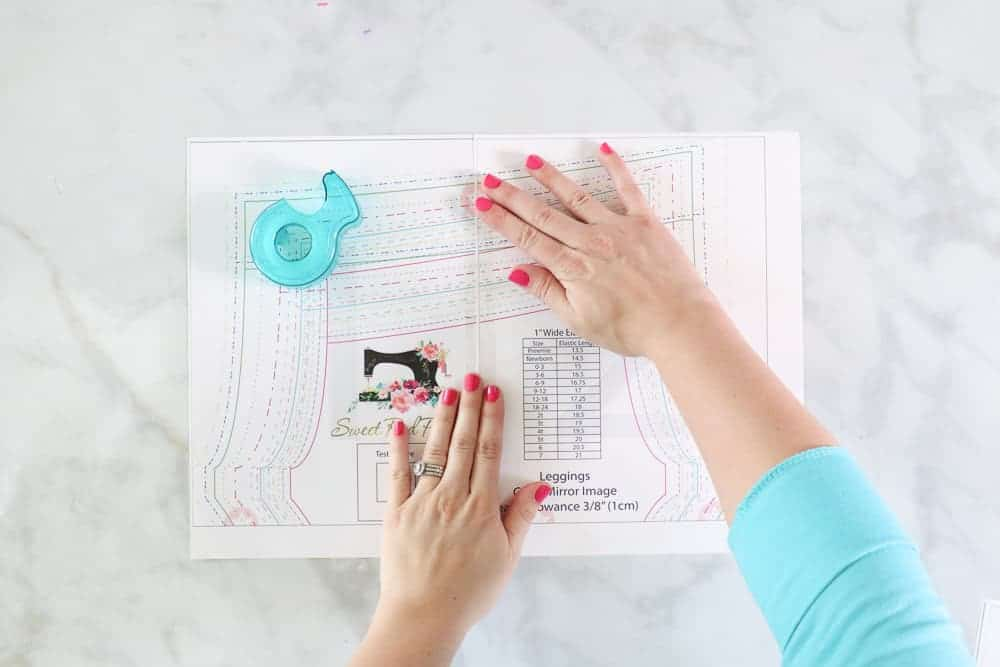 How to piece together a printable sewing pattern |Leggings Pattern by popular US sewing blog, Sweet Red Poppy: image of a woman laying out a kids leggings pattern.