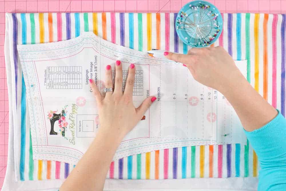 How to cut out fabric leggings |Leggings Pattern by popular US sewing blog, Sweet Red Poppy: image of a woman cutting out kids leggings.