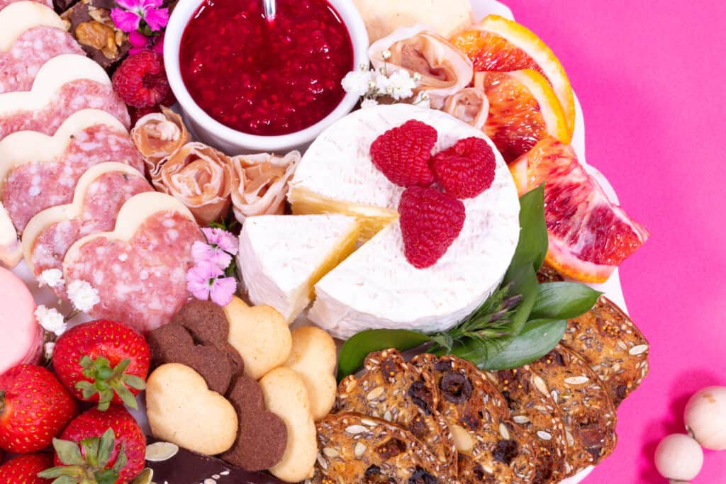 Valentine's Day Charcuterie Board by popular Utah craft blog, Sweet Red Poppy: image of a charcuterie board filled with meat, crackers, cheeses, macaroons, nuts, and fruit.