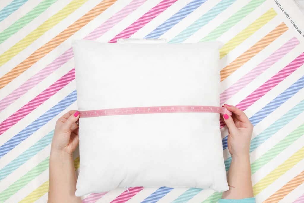 Cut out Fabric for Pillow Case |How to Make an Envelope Pillow Cover With One Piece of Fabric by popular Utah sewing blog, Sweet Red Poppy: image of a woman measuring a square pillow.