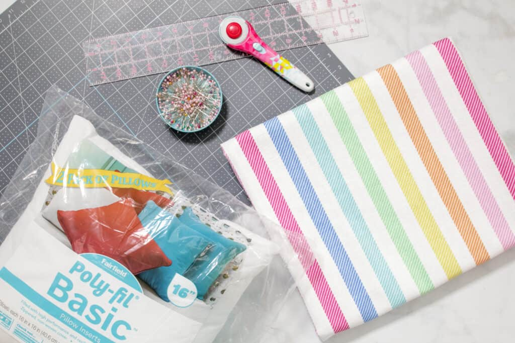 Supplies for Sewing an Envelope Pillow |How to Make an Envelope Pillow Cover With One Piece of Fabric by popular Utah sewing blog, Sweet Red Poppy: image of rainbow stripe fabric, rotary cutter, fabric pins and a rotary board.
