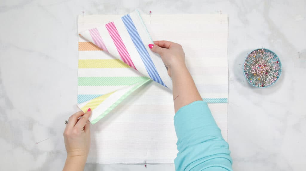 How to Make an Envelope Pillow Cover With One Piece of Fabric by popular Utah sewing blog, Sweet Red Poppy: image of a woman pinning together rainbow stripe fabric.