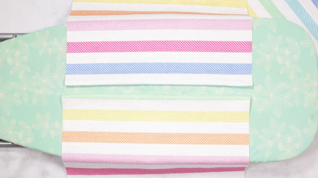 How to Make an Envelope Pillow Cover With One Piece of Fabric by popular Utah sewing blog, Sweet Red Poppy: image of rainbow stripe fabric on a ironing board.