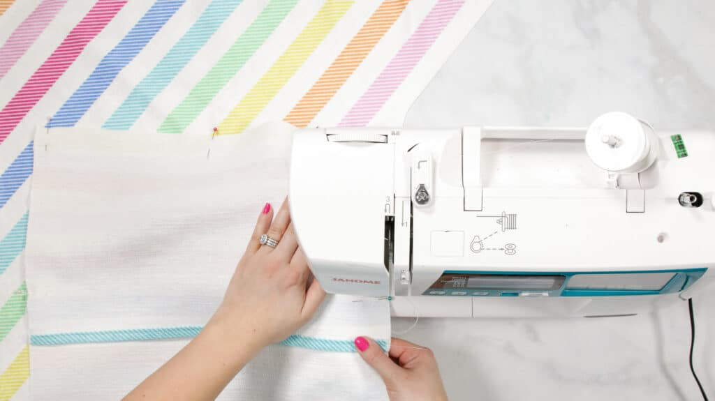 Making an Envelope Pillow Cover Is Easier Than Ever With This Simple Step-by-Step Tutorial and Video Guide! Learn How to Make an Envelope Pillow Cover in Less Than 15 Minutes! |How to Make an Envelope Pillow Cover With One Piece of Fabric by popular Utah sewing blog, Sweet Red Poppy: image of a woman sewing rainbow stripe fabric.