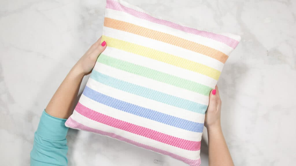 How to Make an Envelope Pillow Cover With One Piece of Fabric by popular Utah sewing blog, Sweet Red Poppy: image of a rainbow stripe pillow cover.