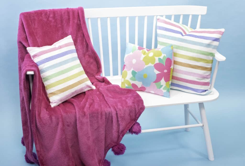 How to Make an Envelope Pillow Cover With One Piece of Fabric by popular Utah sewing blog, Sweet Red Poppy: image of floral print and rainbow stripe print envelope pillow covers on a white bench with a pink throw blanket.