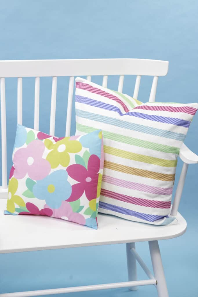 Learn How to Sew an Envelope Pillow Cover |How to Make an Envelope Pillow Cover With One Piece of Fabric by popular Utah sewing blog, Sweet Red Poppy: image of floral print and rainbow stripe print envelope pillow covers on a white bench.
