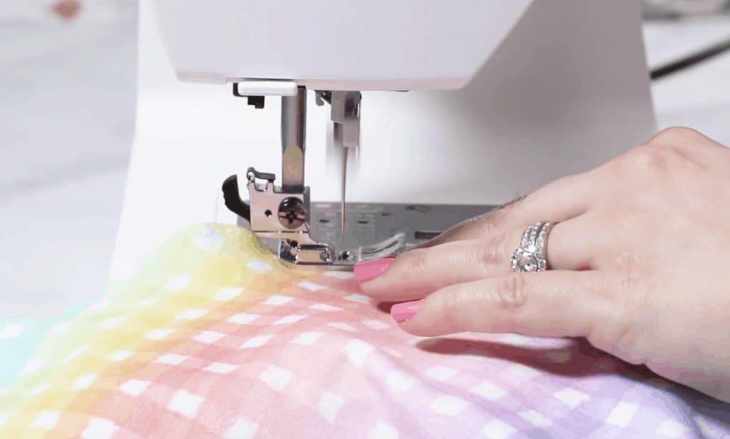 Circle Skirt Hem Method #1  Circle Skirt Dress Pattern by popular Utah sewing blog, Sweet Red Poppy: image of a woman sewing a circle skirt on a sewing machine.