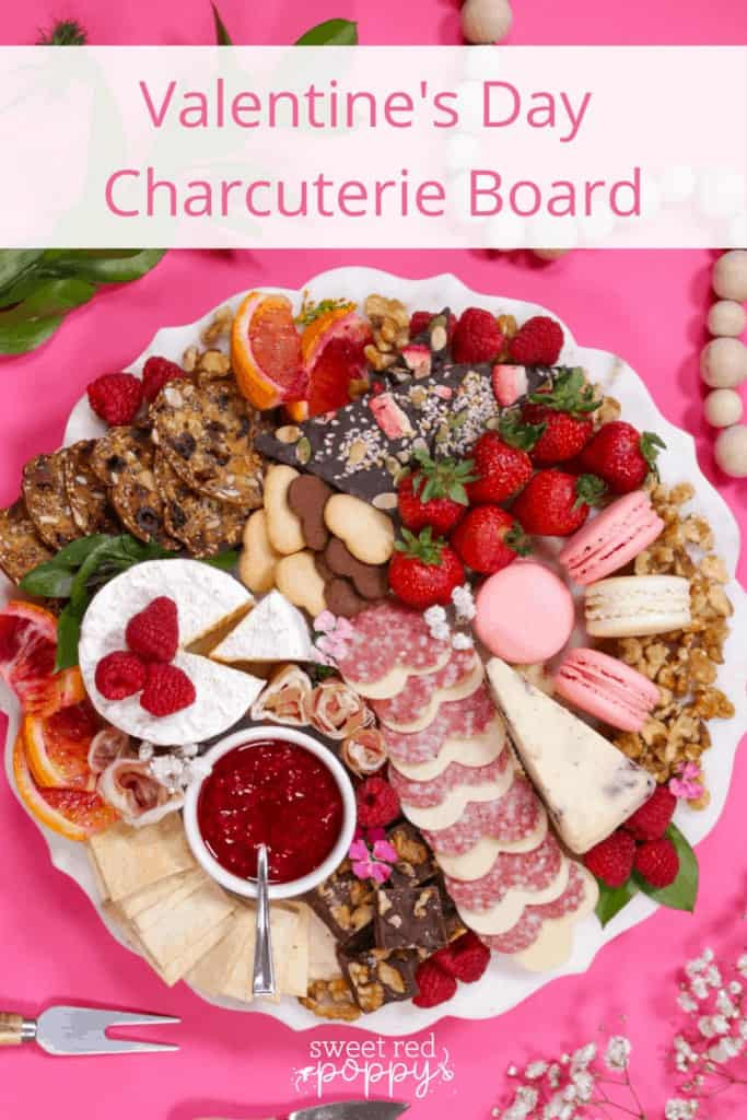 Valentine's Day Charcuterie Board by popular Utah craft blog, Sweet Red Poppy: Pinterest image of a charcuterie board filled with meat, crackers, cheeses, macaroons, nuts, and fruit.