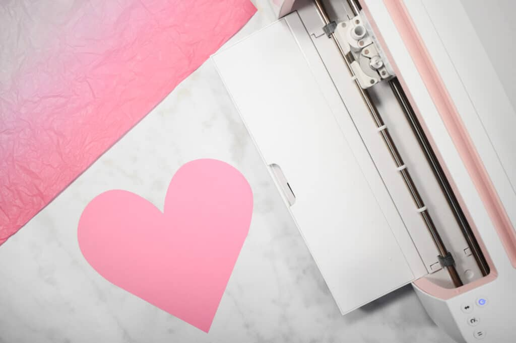 Cricut Shadow Box by popular US craft blog, Sweet Red Poppy: image of  a paper heart next to a Cricut machine.