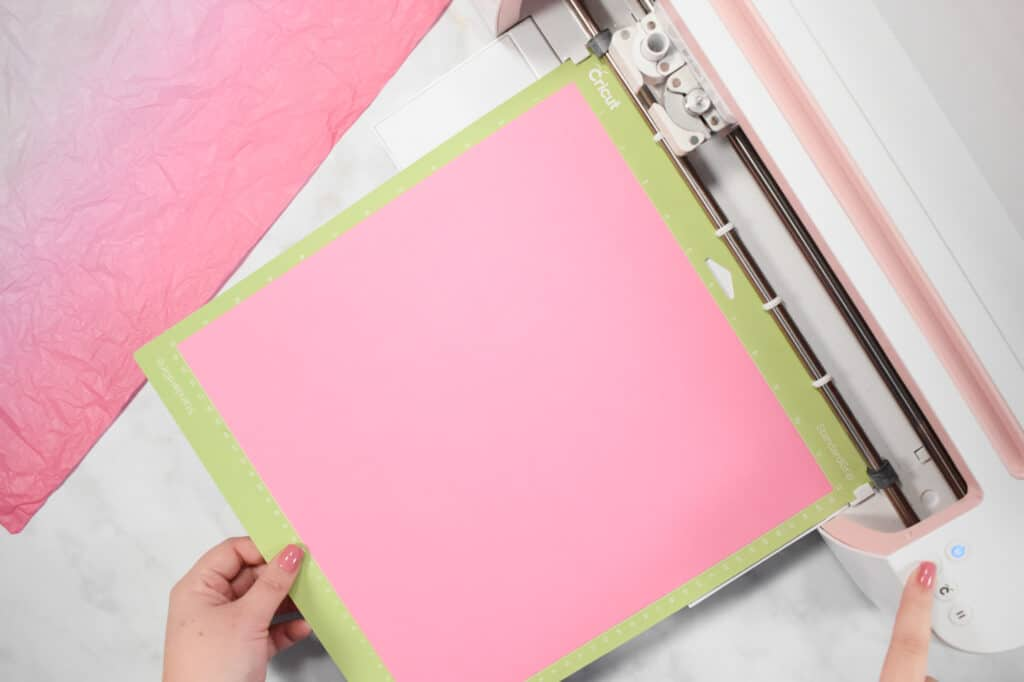 Cricut Shadow Box by popular US craft blog, Sweet Red Poppy: image of  a woman putting pink paper in to a Cricut machine.
