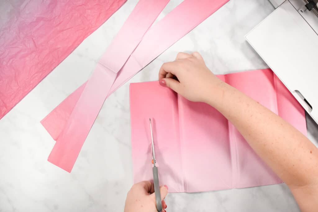 Cricut Shadow Box by popular US craft blog, Sweet Red Poppy: image of  a woman cutting out pink tissue paper squares.