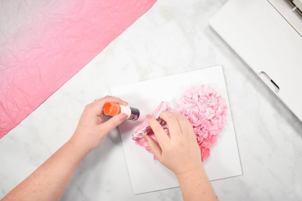Cricut Shadow Box by popular US craft blog, Sweet Red Poppy: image of a woman gluing down a pink paper heart onto a piece of white cardstock.