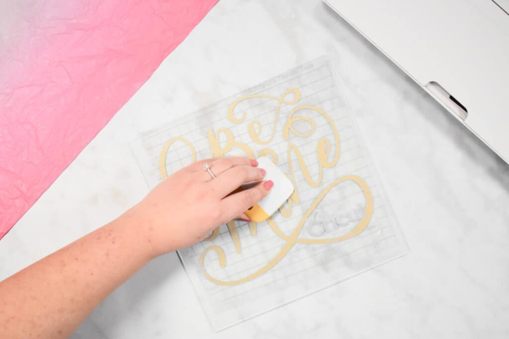 Cricut Shadow Box by popular US craft blog, Sweet Red Poppy: image of  a pressing their scraper tool down onto their vinyl design.