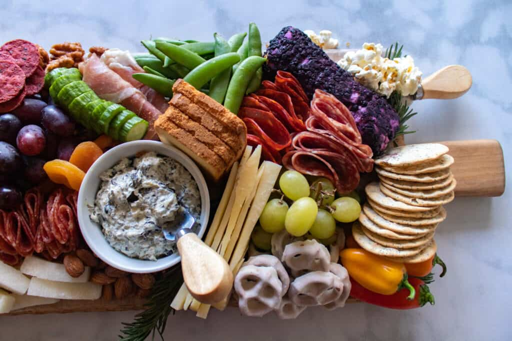 How to Assemble a Charcuterie Board by popular Utah craft blog, Sweet Red Poppy: image of a charcuterie board filled with cheese, nuts, fruit, meat, crackers, dips, vegetables, and yogurt dipped pretzels.