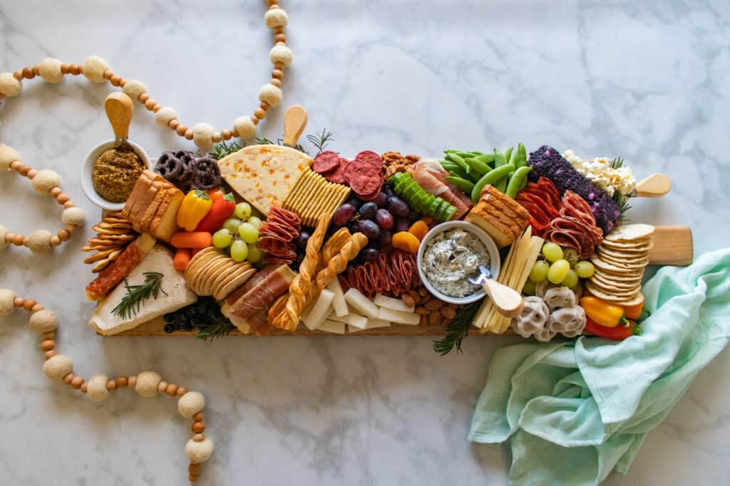 Learn How to Assemble a Charcuterie Board Filled With Cheese, Meats, Crackers, Nuts, Fruits & Vegetables. | How to Assemble a Charcuterie Board by popular Utah craft blog, Sweet Red Poppy: image of a charcuterie board filled with cheese, nuts, fruit, meat, crackers, dips, vegetables, and yogurt dipped pretzels.