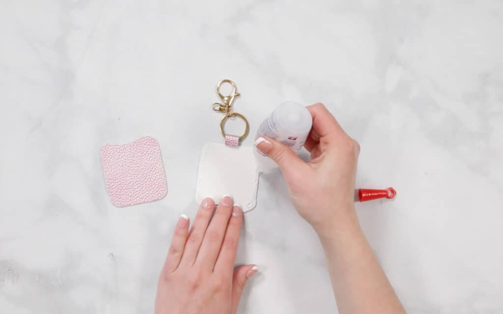 Hand Sanitizer Holder by popular US craft blog, Sweet Red Poppy: image of a woman gluing a no sew hand sanitizer handle.