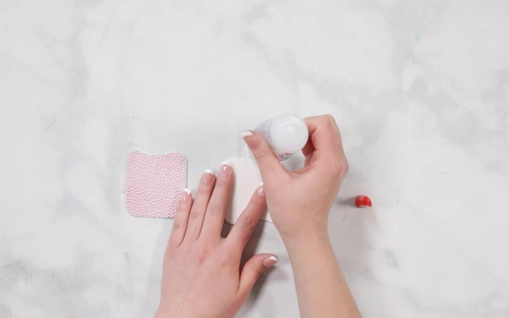 Hand Sanitizer Holder by popular US craft blog, Sweet Red Poppy: image of a woman gluing leather together for no sew hand sanitizer holder.