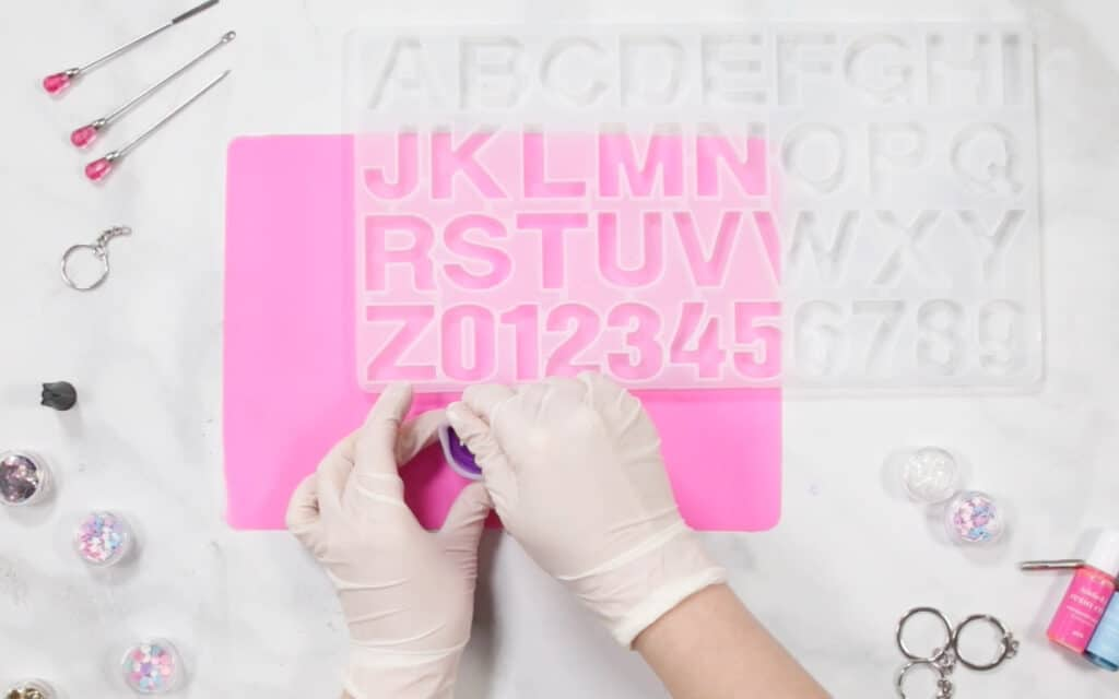 How to Mix UV Resin Colors |Pouring UV Resin |Resin Keychain by popular US craft blog, Sweet Red Poppy: image of a woman pouring resin in to a letter mold.