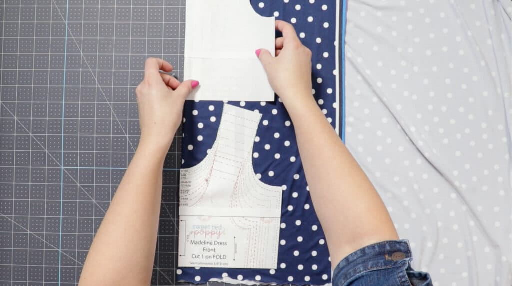 Baby Girl Dress Pattern Free | Circle Skirt Dress Pattern by popular Utah sewing blog, Sweet Red Poppy: image of a woman laying out a circle skirt dress pattern on some blue and white dot knit fabric.
