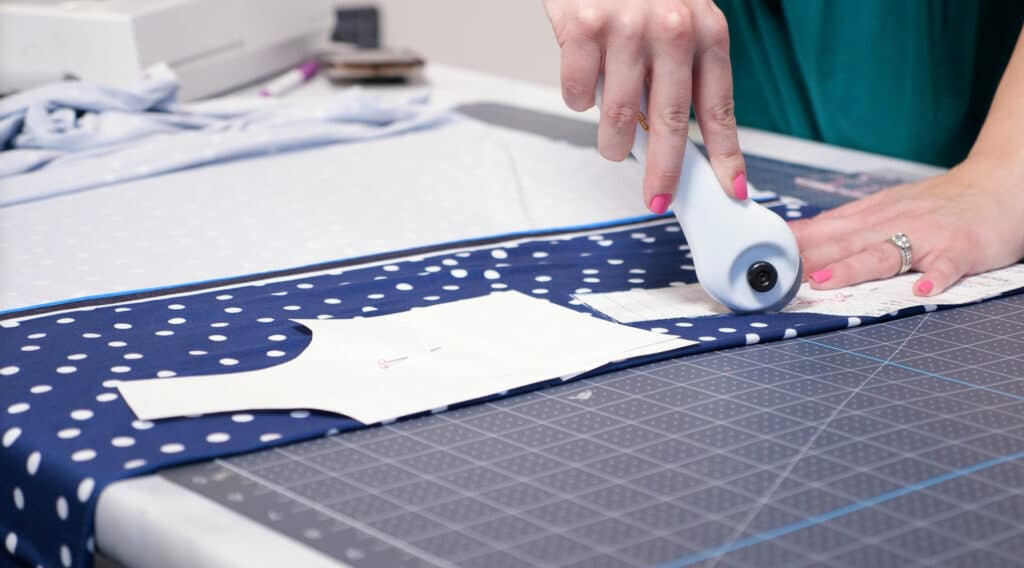 Baby Girl Dress Pattern Free How to Cut out Pattern Pieces | Circle Skirt Dress Pattern by popular Utah sewing blog, Sweet Red Poppy: image of a woman cutting out a circle skirt dress pattern on some blue and white polka dot knit fabric.