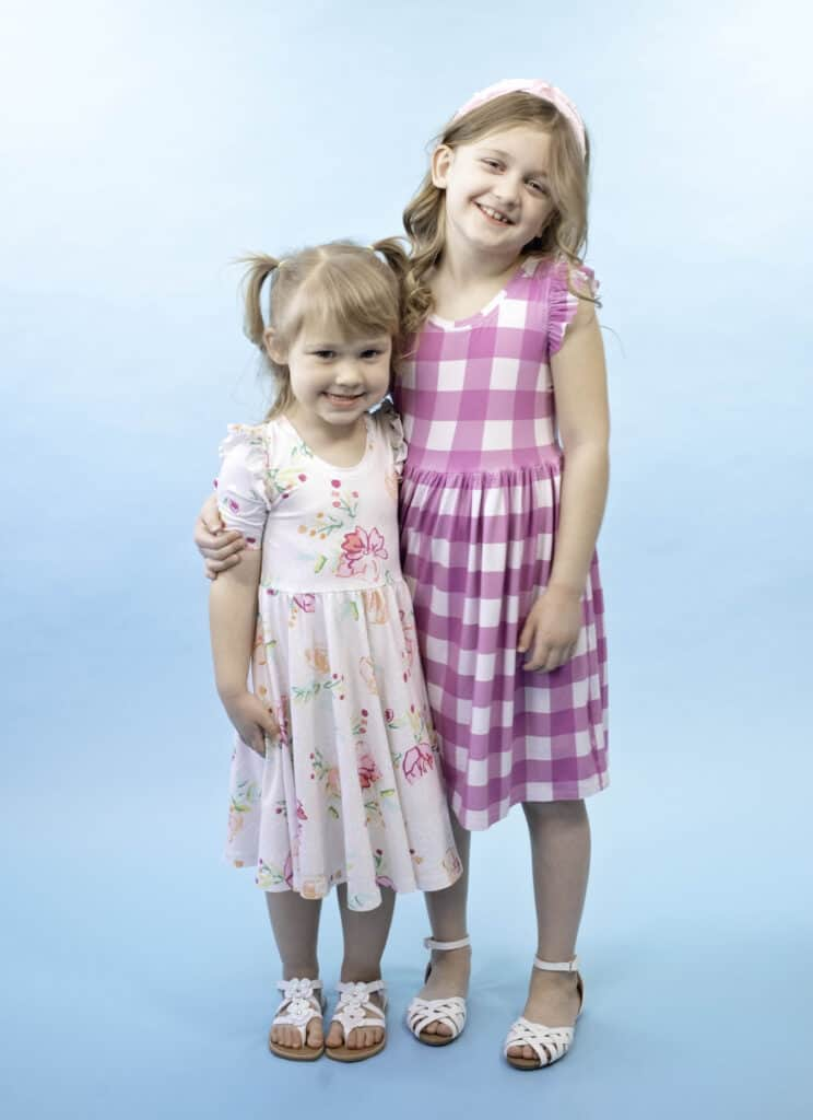 Circle Skirt Dress Pattern by popular Utah sewing blog, Sweet Red Poppy: image of two young girls wearing circle skirt dresses.
