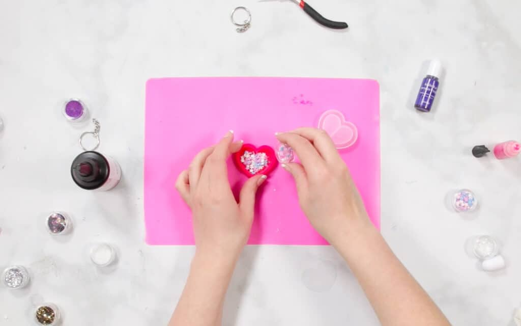 UV Resin by popular US craft blog, Sweet Red Poppy: image of a woman putting glitter n her resin mold on a pink resin mat.