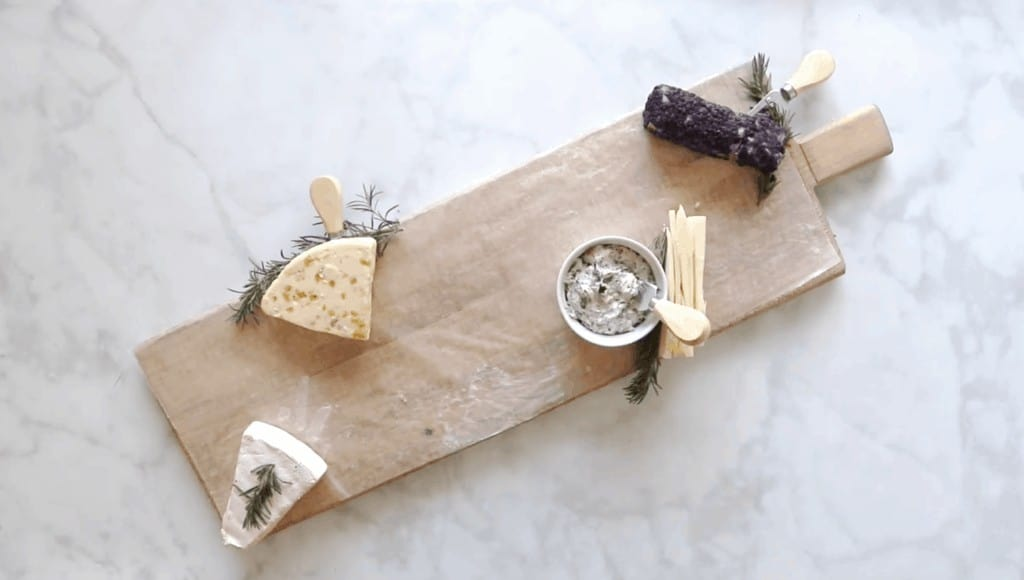 How to Assemble a Charcuterie Board by popular Utah craft blog, Sweet Red Poppy: image of various cheeses on a wooden board.