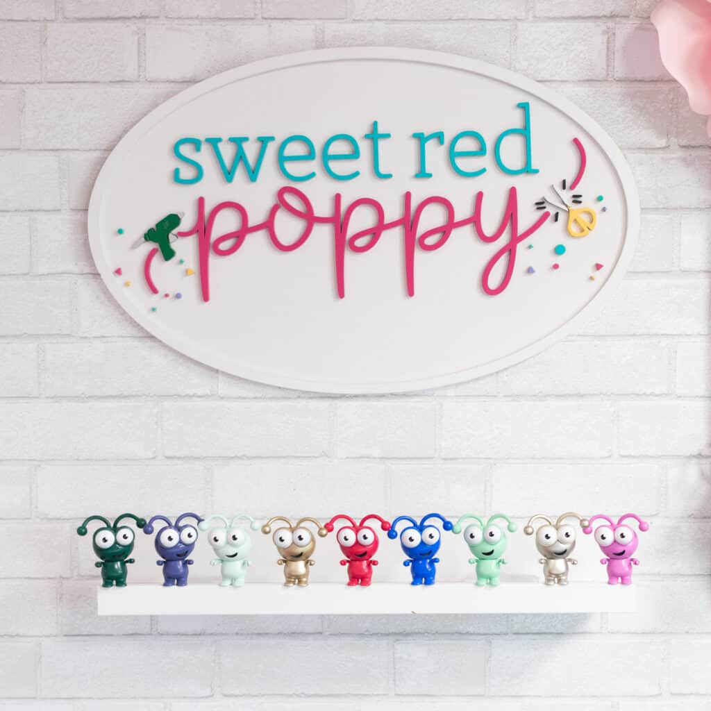 Cricut Mystery Box by popular Utah craft blog, Sweet Red Poppy: image of Cricut cuties on a white floating shelf under a Sweet Red Poppy sign.
