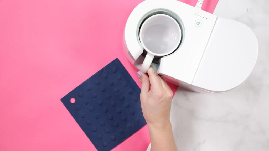 Cricut mug press review featured by top Cricut blogger, Sweet Red Poppy |Cricut Mug Press by popular US craft blog, Sweet Red Poppy: image of a a woman peeling a design backing off of a white ceramic mug.