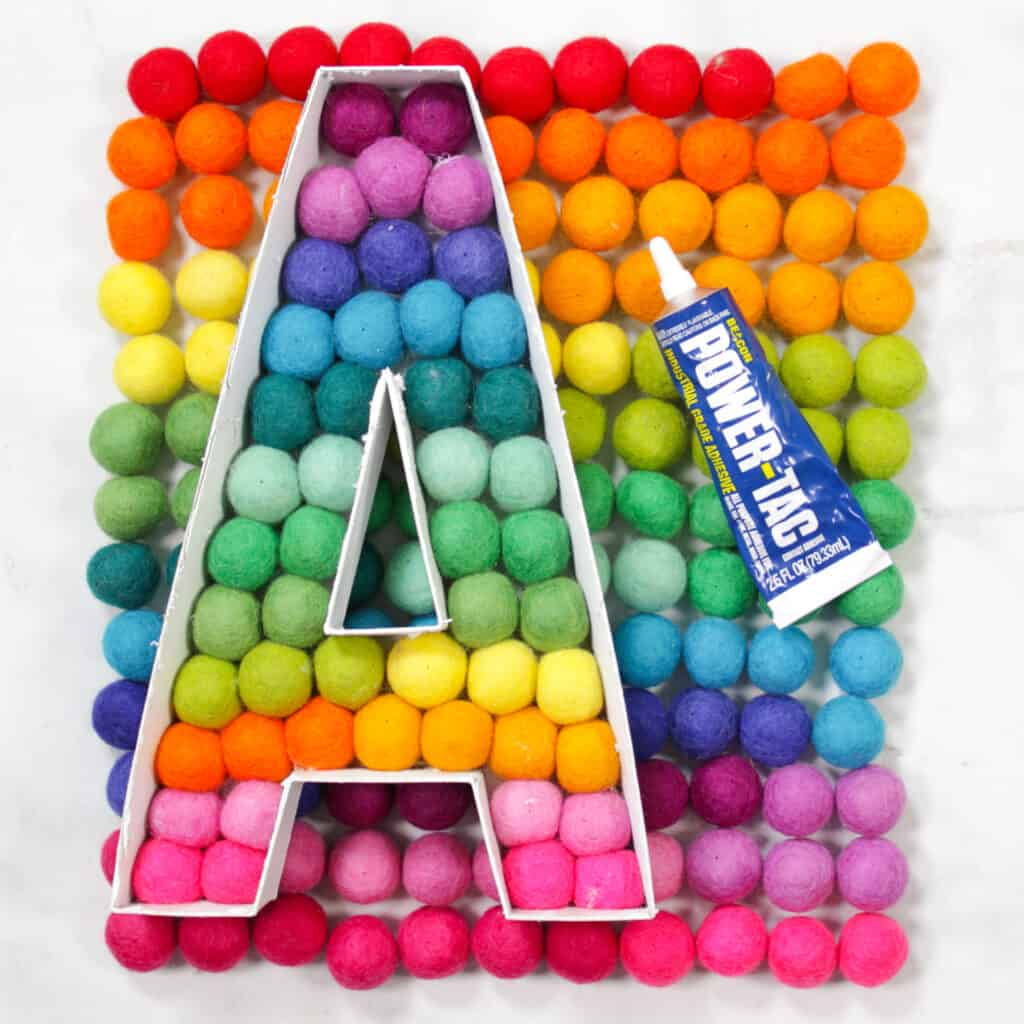 Felt Ball Letters by popular US craft blog, Sweet Red Poppy: image of a letter A filled with rainbow felt balls next to a tube of Power Tac.