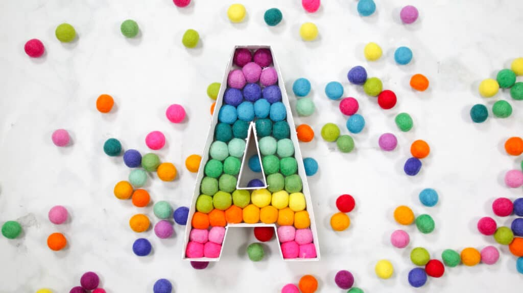 Felt Ball Letters by popular US craft blog, Sweet Red Poppy: image of a white cardboard letter A filled with rainbow felt balls.