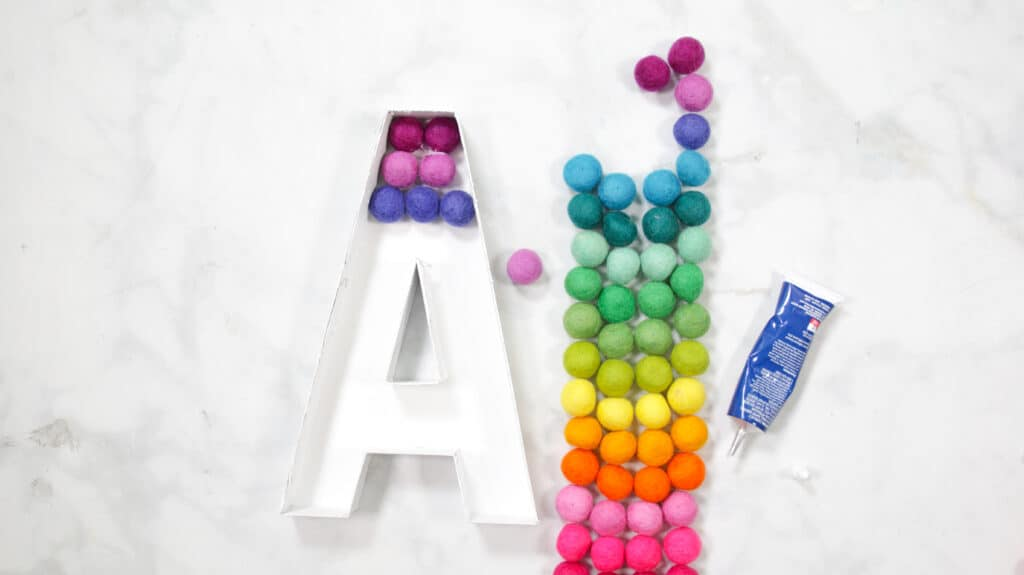 Felt Ball Letters by popular US craft blog, Sweet Red Poppy: image of a white cardboard letter A next to a row  of rainbow felt balls.
