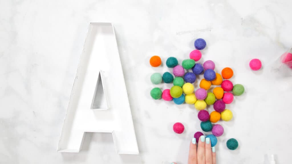 Felt Ball Letters by popular US craft blog, Sweet Red Poppy: image of a white cardboard letter A next to a pile of rainbow felt balls.