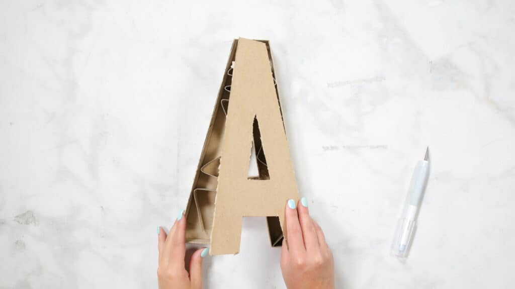 Felt Ball Letters by popular US craft blog, Sweet Red Poppy: image of a woman taking apart a cardboard letter A.