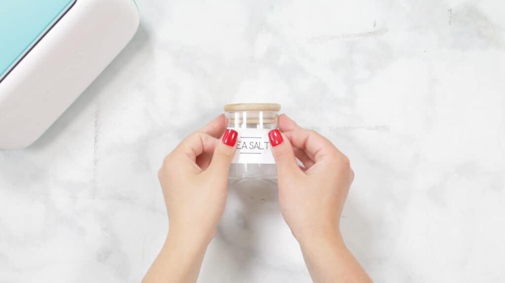 Apply Label |Kitchen Organization Hacks by popular US craft blog, Sweet Red Poppy: image of a woman applying a Cricut Joy Smart Label to a glass spice jar.
