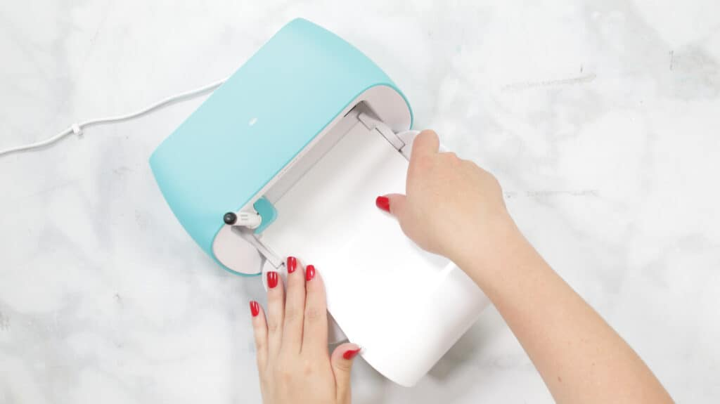 Load Smart Material |Kitchen Organization Hacks by popular US craft blog, Sweet Red Poppy: image of a woman loading Cricut smart material.