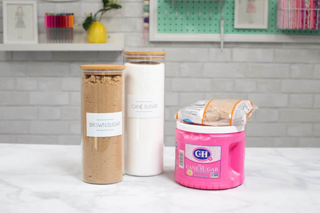 Pantry Item Labels |Kitchen Organization Hacks by popular US craft blog, Sweet Red Poppy: image of glass jars with Cricut labels next to a jar of cane sugar and a bag of brown sugar.