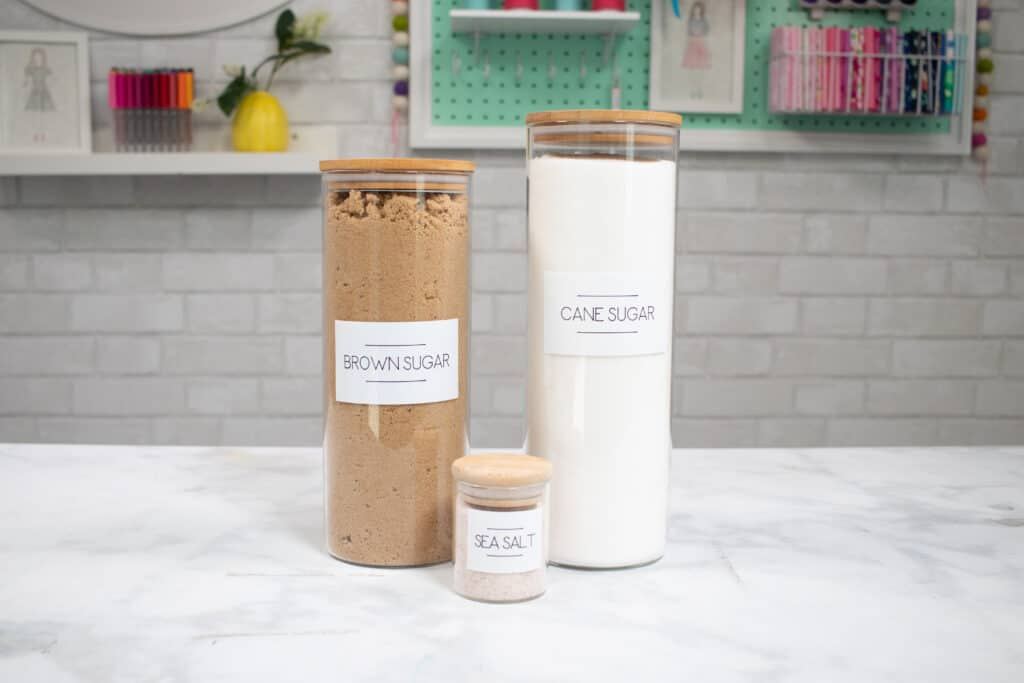 Label all of your pantry items. | Kitchen Organization Hacks by popular US craft blog, Sweet Red Poppy: image of glass jars containing cane sugar, brown sugar, and sea salt with Cricut labels on them.