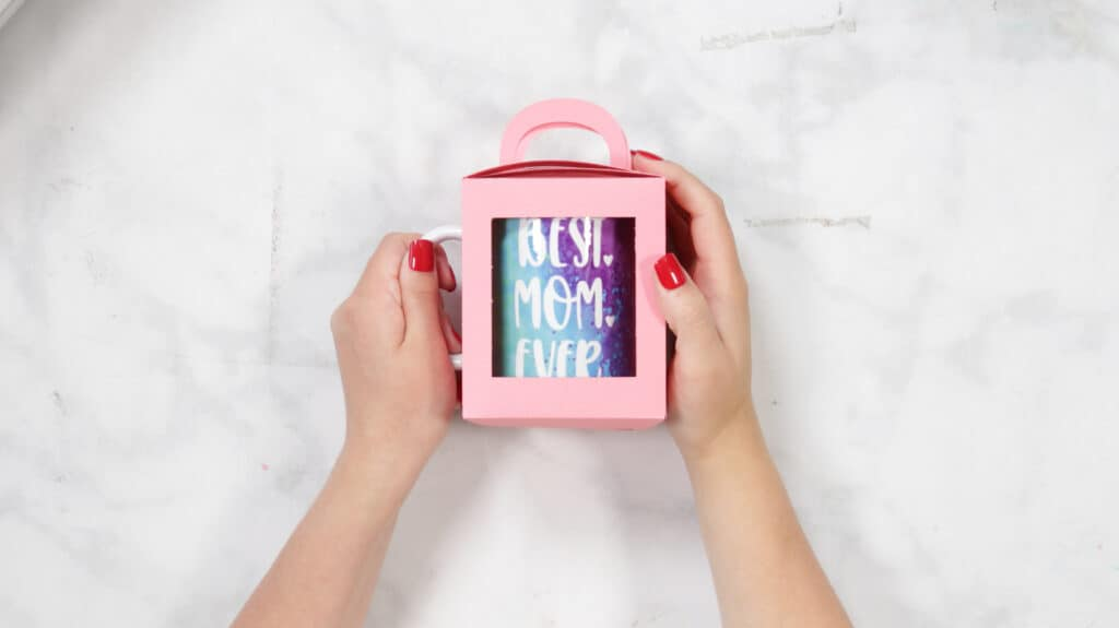 Finished Mother's Day Mug Box |Mother's Day Mug by popular US craft blog, Sweet Red Poppy: image of a woman putting a mug in a cardboard gift box.