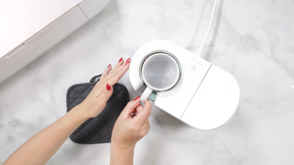 Remove Mug |Mother's Day Mug by popular US craft blog, Sweet Red Poppy: image of a woman using a Cricut mug press.