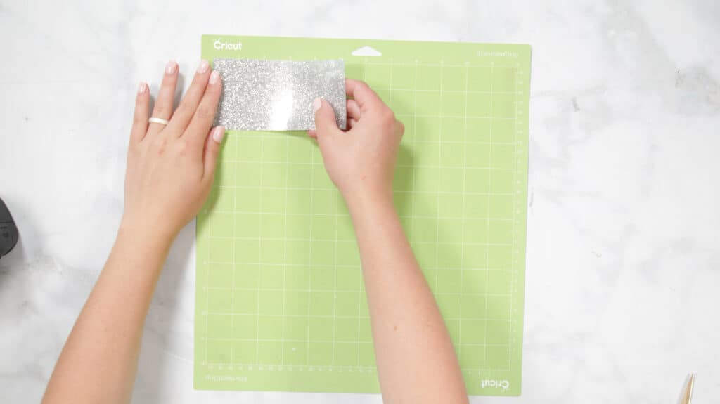 Cricut Explore 3 by popular US craft blog, Sweet Red Poppy: image of a woman putting Cricut smart iron on on a Cricut cutting board.