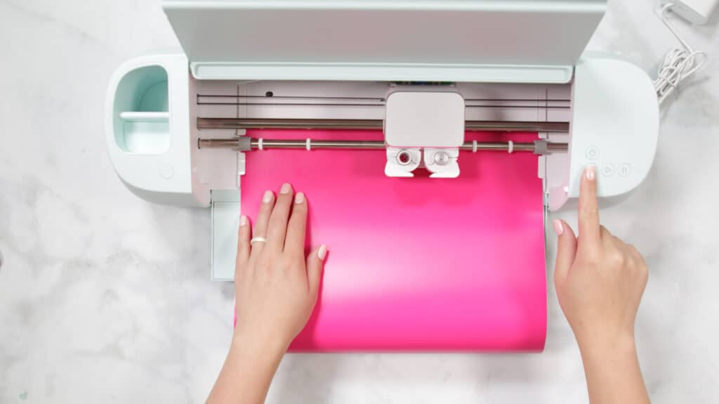 Cricut Explore 3 by popular US craft blog, Sweet Red Poppy: image of a woman putting pink vinyl in a Cricut Explore 3.