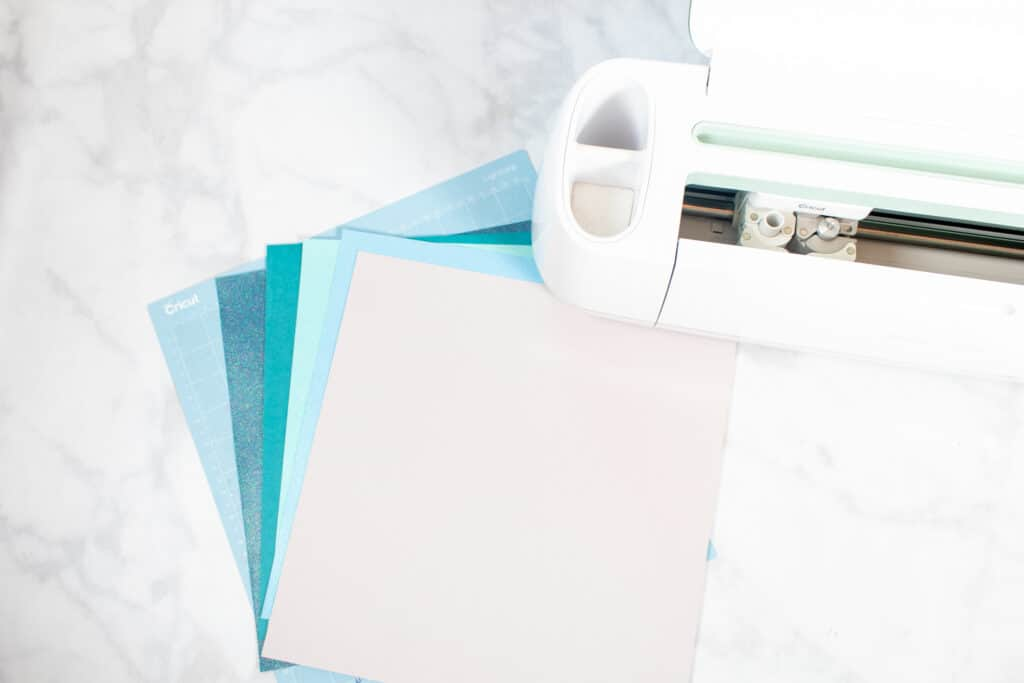 DIY Father's Day Card by popular US craft blog, Sweet Red Poppy: image of blue and white Cricut paper next to a Cricut machine.