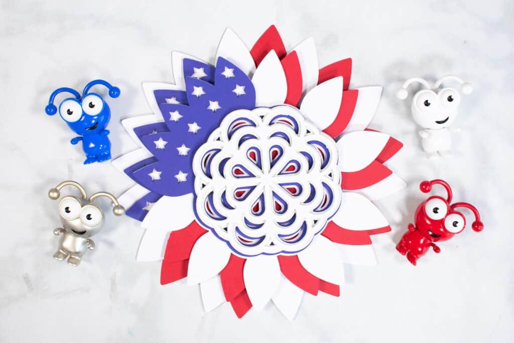 DIY 4. Juli Kranz vom beliebten US-Handwerksblog Sweet Red Poppy: Bild eines geschichteten DIY 4. Juli Kranzes, umgeben von einigen roten, weißen, blauen und silbernen Cricut-Maskottchen.