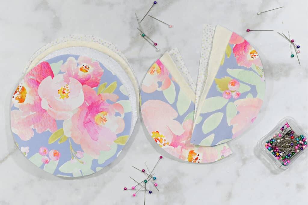 Oven Mitt Sewing Pattern by popular US sewing blog, Sweet Red Poppy: image of circular pieces of fabric cut in half and stacked together and resting next to a clear plastic box of sewing pins.