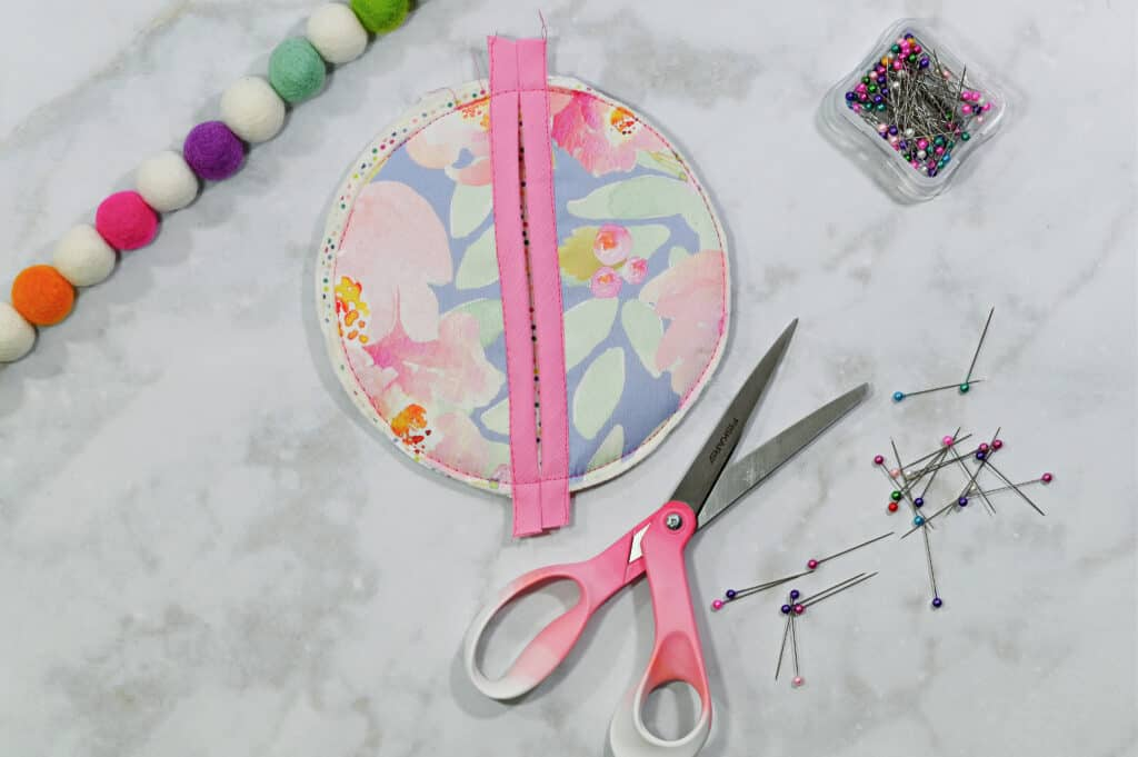 Oven Mitt Sewing Pattern by popular US sewing blog, Sweet Red Poppy: image of a floral fabric oven mitt resting next to some fabric scissors and fabric pins.