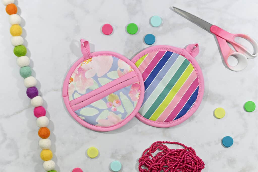 Oven Mitt Sewing Pattern by popular US sewing blog, Sweet Red Poppy: image of a floral fabric and rainbow stripe fabric oven mitts next to a pair of fabric scissors and rainbow felt Pom Pom garland.