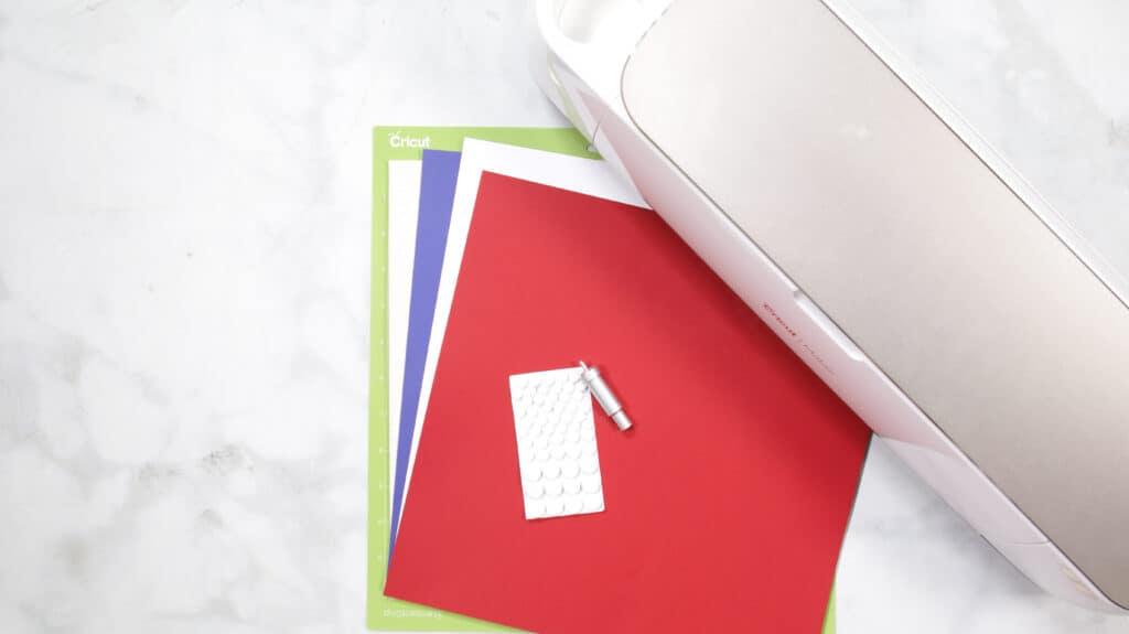 DIY 4. Juli Kranz vom beliebten US-Handwerksblog Sweet Red Poppy: Bild von rotem, weißem und blauem Papier neben einer Cricut-Maschine.